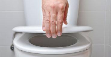 mão levantando tampa de assento de vaso sanitário