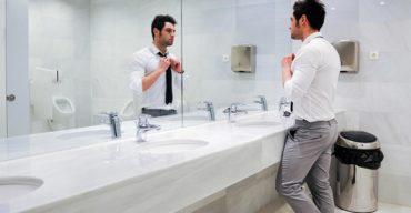 Homem usando o banheiro comercial pensando em implantar tecnologia no banheiro